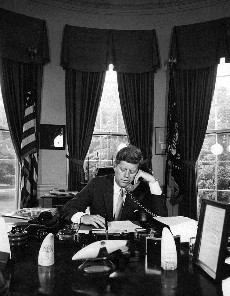 23 August 1962: President Kennedy addresses the AMVETS convention in New York City by telephone. White House, Oval Office. Photo credit: Abbie Rowe, National Park Service, in the John F. Kennedy Presidential Library and Museum, Boston.