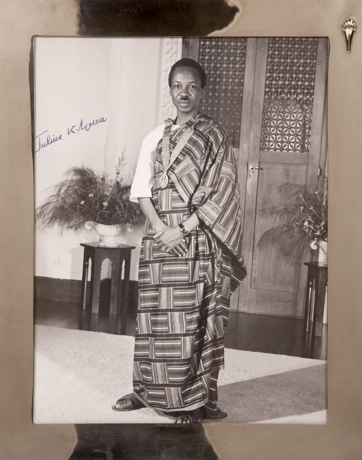 A rare portrait of   Julius K. Nyerere, President of Tanganyika (Tanzania). He is wearing traditional African dress with a medal around his neck. He stands in front of an ornately carved wood door flanked by two floral arrangements. The photograph is in a silver frame. Historical Note: This photograph was presented to President John F. Kennedy by Julius K. Nyerere, Prime Minister of Tanganyika (1961), President of Tanzania (1964-1985), during his state visit to the White House July 15, 1963.