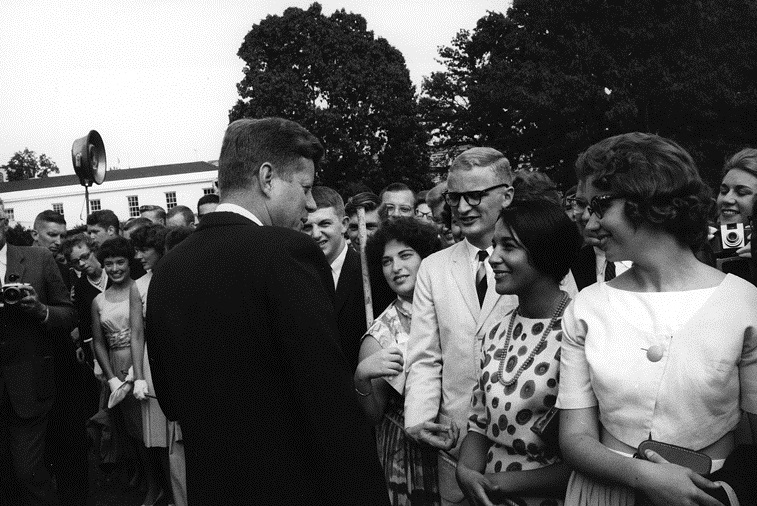 "August 9, 1962: 633 Peace Corps trainees preparing in the Washington area for overseas assignments visited President Kennedy on the south lawn of the White House. The President welcomed the trainees with special pleasure because they had ""committed themselves to a great adventure.""  He repeated his hope that Peace Corps Volunteers would return to careers of service in the Government. After informal conversation with the trainees, the President on the spur of the moment ordered a special tour of the White House for the trainees.""  Photograph by Rowland Scherman, Peace Corps, in the John F. Kennedy Presidential Library and Museum, Boston."