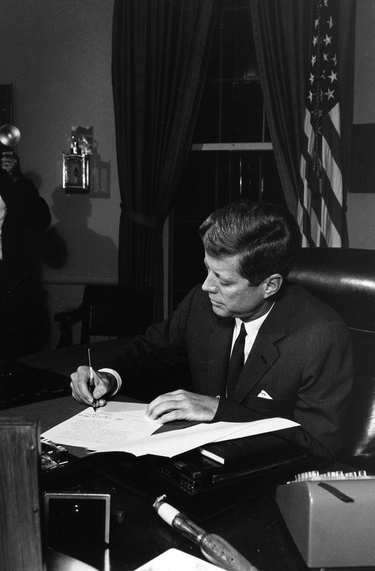 ST-459-10-62  23 October 1962  President Kennedy signs the Proclamation for Interdiction of the Delivery of Offensive Weapons to Cuba. White House, Oval Office. Photograph by Cecil Stoughton, White House, in the John F. Kennedy Presidential Library and Museum, Boston.