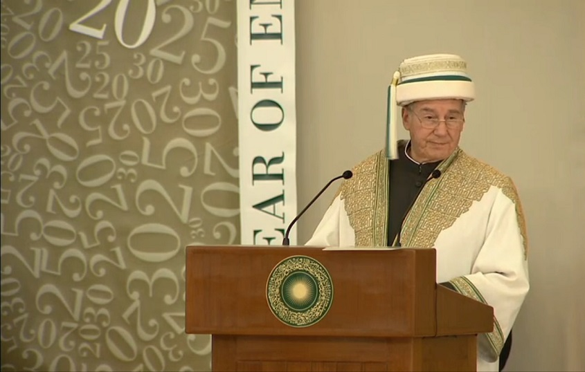 "His Highness the Aga Khan addressing a large crowd at the 2013 Convocation Ceremony, the 30th Anniversary of the Aga Khan University which he built in 1983. His ancestor, the Fatimid Imam-Caliph Al-Muizz built the Al-Azhar University in Cairo, a thousand years ago. His Highness, as the Chancellor of the University, is seen in the academic regalia called Jamiapoash which comprises  a Khila'at, meaning ""robe of honour"" in Arabic and a Sirpoash, meaning ""headwear"" in Persian, with a tassel on the right. The Aga Khan's robe is distinguished by its very elaborate and intricate gold embroidery on the upper part of the robe both back and front, but is also unique for its white colour"