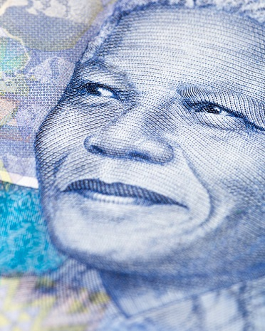 A close-up of a detail of a South African Hundred Rand banknote, featuring an engraving of the face of iconic statesman Nelson Mandela, giving his trademark smile. South African wildlife and African designs form the watermarked background. Photo: Istockphoto. Copyright.