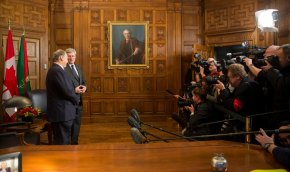 His Highness the Aga Khan and the Right Honourable Stephen Harper, the Prime Minister of Canada, face eager cameras at the Canadian Parliament Building on Thursday, 27 February, 2014. An oil on canvas painting of The Right Honourable Sir John Alexander Macdonald, Prime Minister (1867-1873; 1878-1891) adorns a wall as part of the House of Commons Heritage Collection, while the Ismaili Imamat and Canadian Flags form a backdrop in this historical photo. Photo credit: The Office of the Prime Minister of Canada.