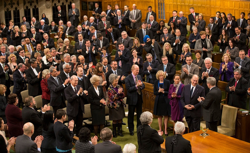 """His Highness the Aga Khan is applauded by the Prime Minister, Members of the House, as well as other distinguished visitors as he arrives in the House of Commons on Thursday, February 27, 2014 to deliver a rare address - the first by a faith leader in 75 years. The Ottawa Citizen published a similar photo on its front page of Friday February 28, giving it the title """"In Divine Company."""" Alongside the Ismaili Imam are his daughter Princess Zahra and the Prime Minister's wife, Laureen Harper. Others in the photo, in rows adjacent to Mrs. Harper (l to r) -- 1st row: The Aga Khan's younger brother, Prince Amyn Muhammad Aga Khan, Chief Justice of the Supreme Court of Canada, The Right Honourable Beverly McLachlin, Former Governor General of Canada, The Right Honourable Adrienne Clarkson, and renowned Canadian author, intellectual and philosopher, John Ralston Saul; 2nd row (l to r). President Malik Talib of the Aga Khan Ismaili Council for Canada, Prince Hussain Aga Khan, Princess Salwa Aga Khan and her husband Prince Rahim Aga Khan - with both the Princes in the row being the Aga Khan's children. Photo credit: The Office of the Prime Minister of Canada."""