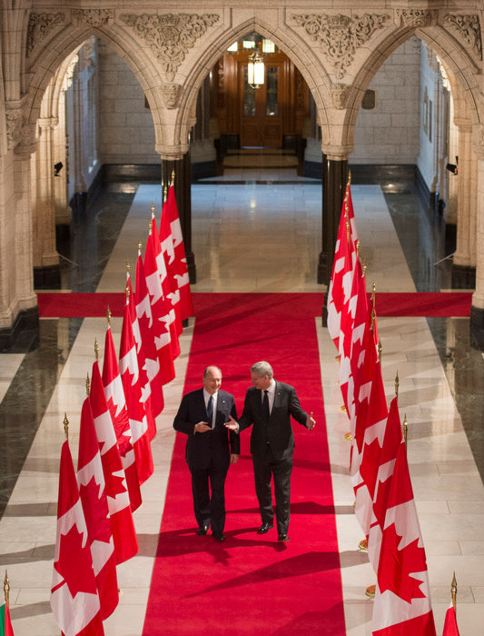 His Highness the Aga Khan and Prime Minister Stephen Harper walk the Hall of Honour at the Parliament of Canada. where His Highness delivered an address to both the Houses on Thursday, February 27, 2014. This impressive ceremonial hall is used for state occasions, parliamentary events, and formal processions such as the Speaker's Parade. The Hall of Honour is part of the central axis of the Centre Block, joining Confederation Hall to the Library of Parliament, and providing access to the main committee rooms. Photo credit: The Office of the Prime Minister of Canada.