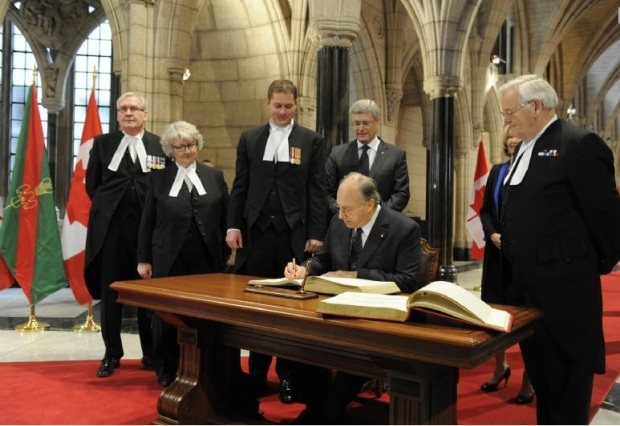 His Highness the Aga Khan signs the visitors books for the House of Commons and the Senate in the Canadian Parliament Rotunda as Prime Minister Stephen Harper, his wife Laureen Harper, The Honourable Andrew Scheer, Speaker of the House of Commons and the Honourable Noël Kinsella, Speaker of the Senate, and other individuals look on. Photo credit: TheIsmaili/Gary Otte.