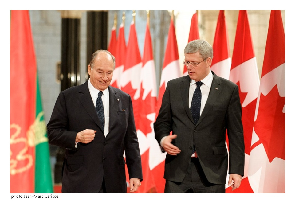 His Highness the Aga Khan and Prime Minister Harper in a conversation as they proceed to the signing ceremony of the protocol of understanding between the Ismaili Imamat and Canada. They are flanked on either side by the red and green flag of the Ismaili Imamat and the maple leaf flag of Canada. Photo: Jean-Marc Carisse. Copyright.