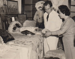 Portuguese crafts teacher shows Mawlana Hazar Imam a collection of needlework prepared by Ismaili students who regularly attended her sessions in a classroom located on the main floor of the Lourenço Marques jamatkhana. Mawlana Hazar Imam visited the Portuguese colonial city in 1959, following a visit made by his beloved father, Prince Aly Khan, in 1958. See photos below. Photo: Jehangir Merchant Collection.
