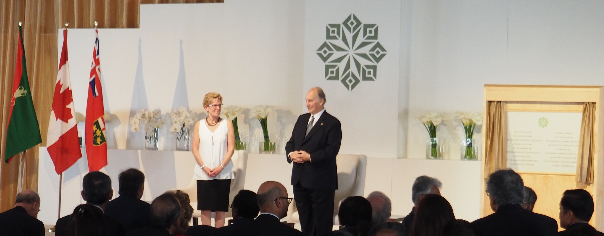 Mawlana Hazar Imam and Premier Kathleen Wynne prepare to depart after unveiling the plaque to open the Aga Khan Park on May 25, 2015. Also seen  in the photo are the logo of the the Aga Khan Park and the flags of the Ismaili Imamat (left), Canada, and the Province of Ontario. Photo: Simerg/Malik Merchant. Copyright.
