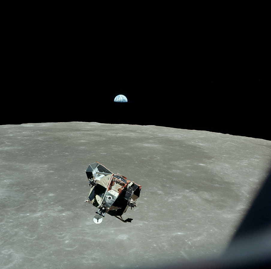 AS11-44-6642_LM approaches CSM for docking with earthrise in b.g.