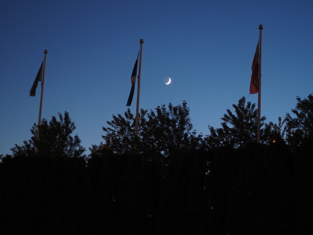 9:09 -10:40 PM: A view of the Crescent Moon from the Aga Khan Park on July 23, 2020, with flags of the Ismaili Imamat, the City of Toronto and the Province of Ontario in the foreground. Photo: Malik Merchant / Simergphotos.