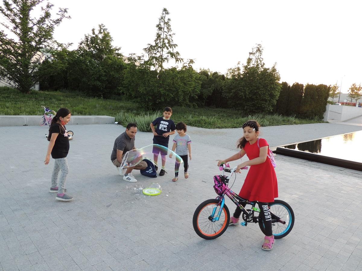Children enjoy soap balloons by a pond at Aga Khan Park.